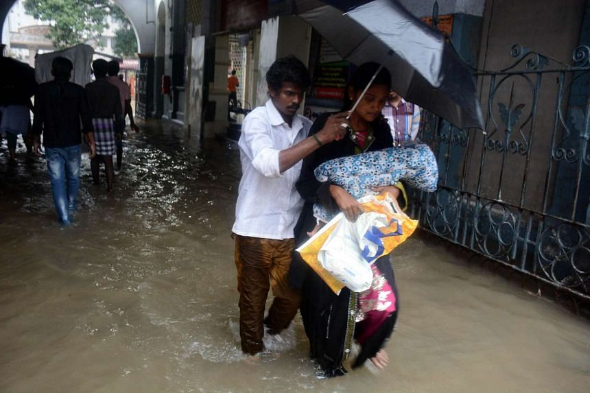 An Indian couple shelter under an umbrella as they walk with their child through floodwaters.