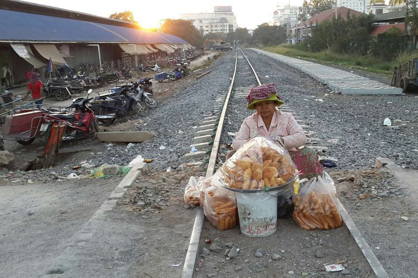 A food vendor sells her wares on disused rail tracks in Aranyaprathet, the Thai border town just next to the Cambodian casino town of Poipet.