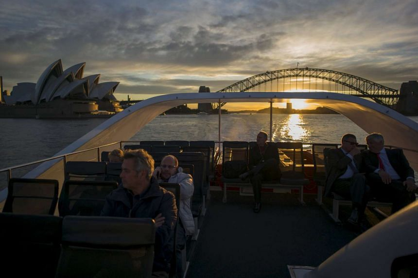 Commuters ride on the rooftop deck of a Sydney ferry at sunset en route to Rose Bay in Sydney's eastern suburbs.