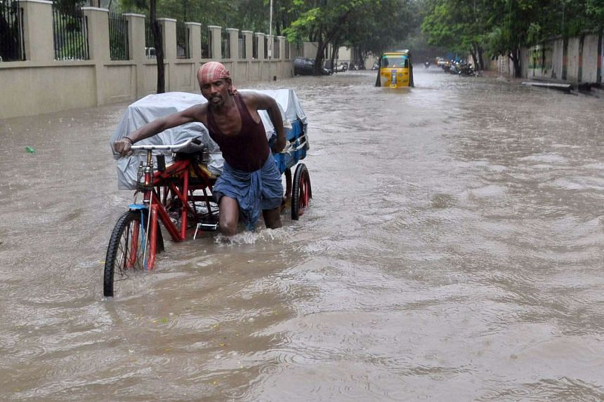 An Indian labourer pushes his trishaw through floodwaters in Chennai on Dec 1, 2015.