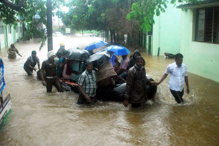 Indian rescue workers and volunteers use an inflatable boat to take residents through floodwaters.