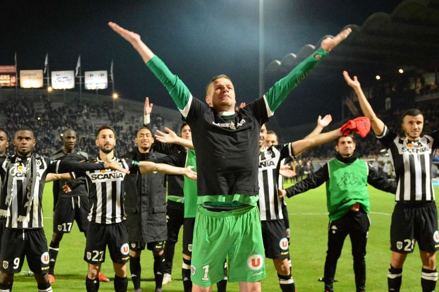 Angers' French goalkeeper Ludovic Butelle and his teammates gesture during the French L1 football match between Angers (SCO) and Paris Saint-Germain (PSG), on December 1, 2015, at the Jean Bouin stadium, in Angers, western France. The match ended in