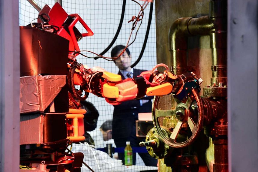 Humanoid robot Jaxon turns a handle of a valve during a demonstration of how the robot would work within a disaster area.