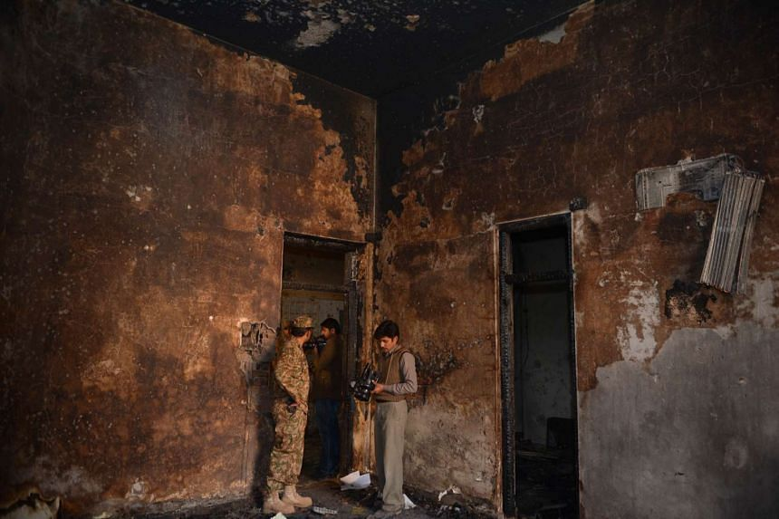 A Pakistani army soldier shows a burnt room to media representatives at an army-run school a day after an attack by Taleban militants in Peshawar.