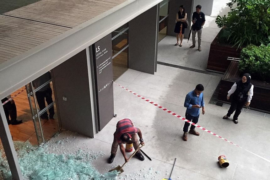 The shattered glass door (left) on Level 5 of the National Gallery, and workers (above) putting up a screen in the area yesterday. A man suffered minor abrasions on his right hand in the incident.