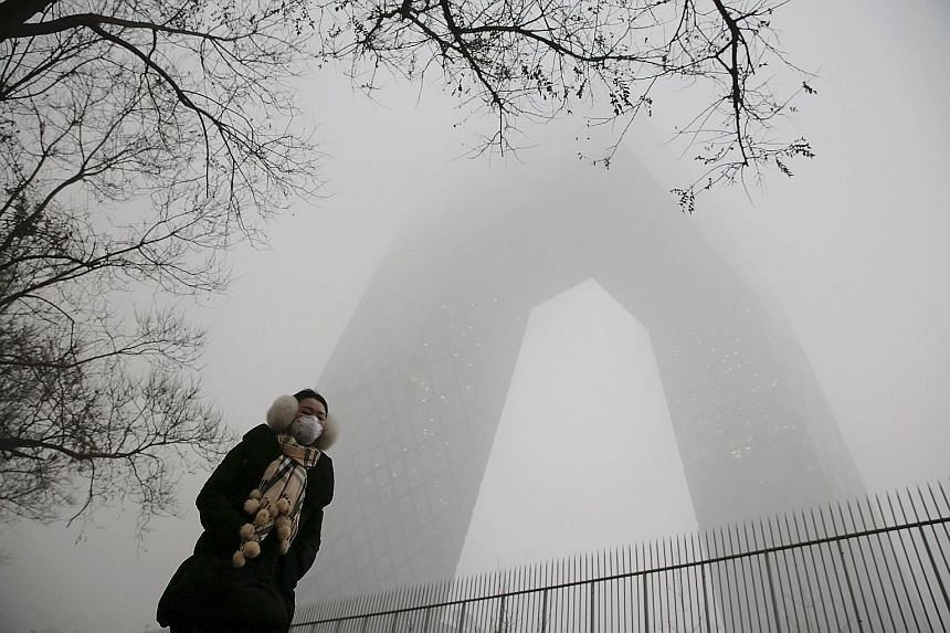A woman walking past the China Central Television building in Beijing, which was barely visible yesterday. While the Chinese capital often battles with air pollution, the current round of smog is the most severe to hit the city this year. Experts say