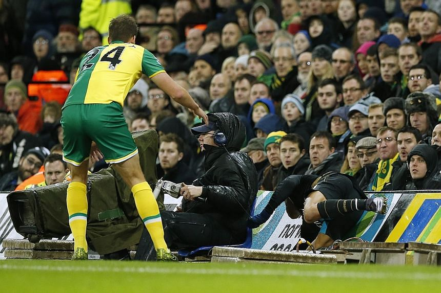 Arsenal's Alexis Sanchez crashes into the advertising boards as Norwich's Ryan Bennett looks on. The Gunners are hoping that Sanchez has pulled his hamstring instead of tearing it, as this will involve a quicker recovery.