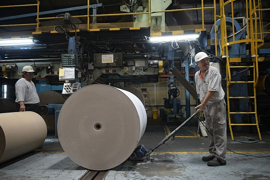 TCG Rengo's machine operator Wan Eng Kok, 60, using a device that helps push paper rolls that often weigh a tonne or more. The company has invested in such equipment to help reduce the manual demands on its older workers.