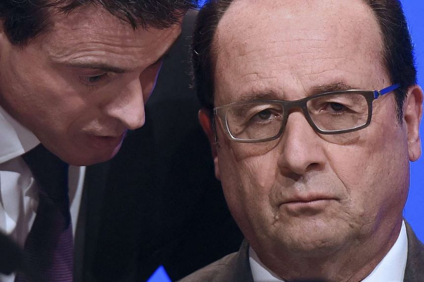 French Prime Minister Manuel Valls (left) speaks to Hollande before he delivers a speech.