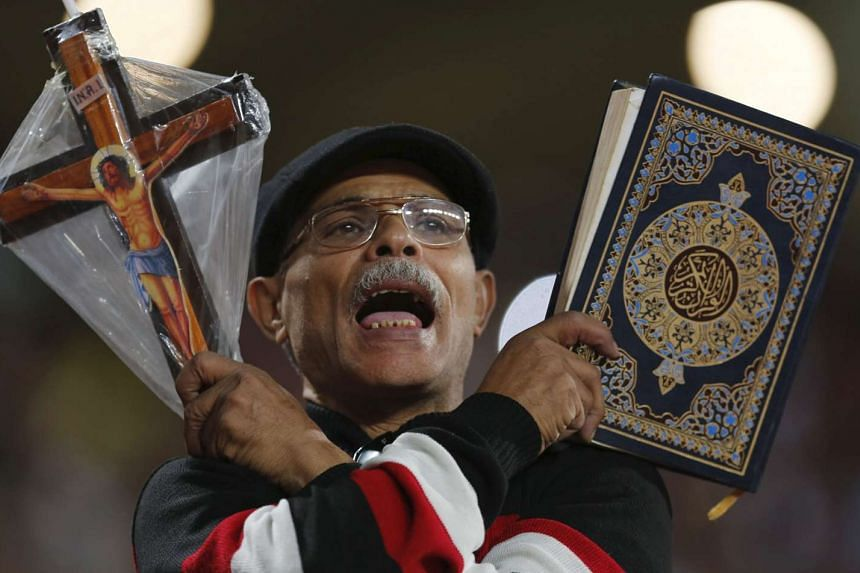 An Egyptian fan holding a Quran and a cross at a 2018 World Cup qualifying football match against Chad on Nov 17.