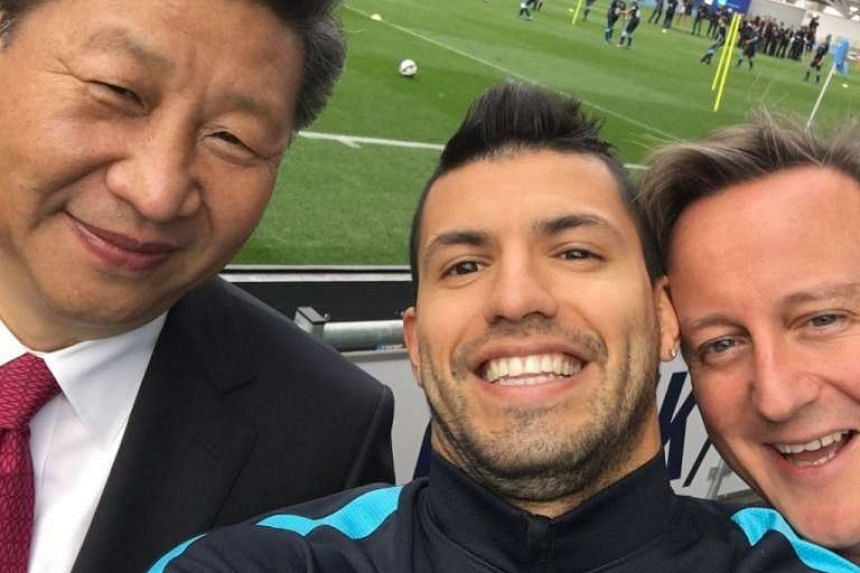 Xi poses for a selfie with footballer Sergio Aguero (centre) and British PM David Cameron at Manchester City.