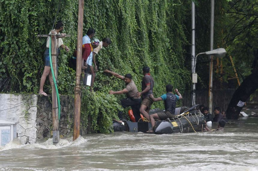 Indian policemen rescue people from flood waters in Chennai, India on Dec 2, 2015.