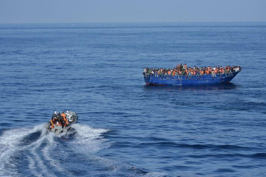 Spanish rescuers approaching a boat with migrants off the coast of Libya.