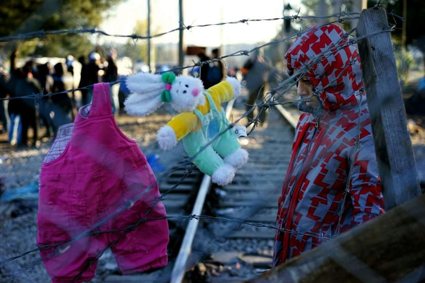 A migrant boy from Pakistan stand behind the fence, waiting to cross the border near Gevgelija.