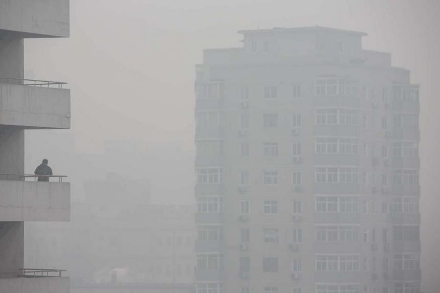 A man stands on a balcony among buildings shrouded in haze in Beijing, China.