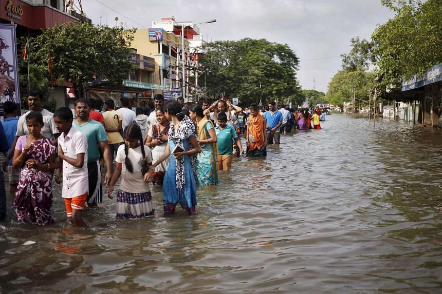 Residents wade through a flooded street as they evacuate their homes in Chennai.