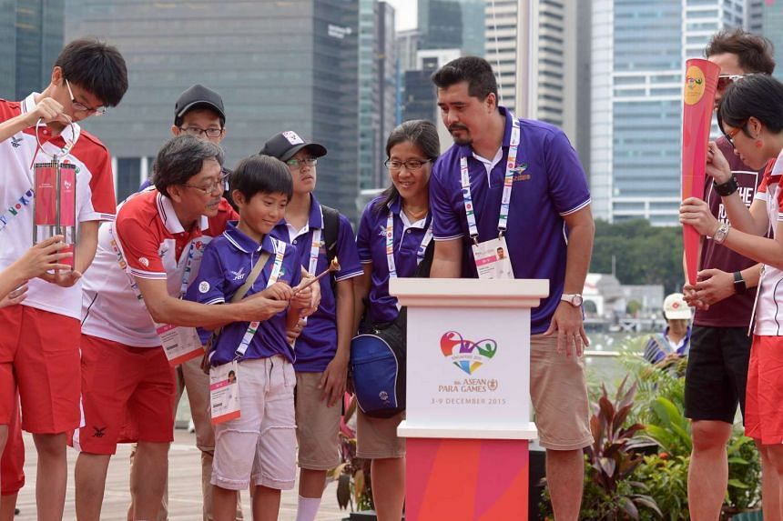 Deshann Cayden Ooi (third from left) holds a flame from the safety lantern during the start of the 8th Asean Para Games Torch Parade on Dec 3, 2015.