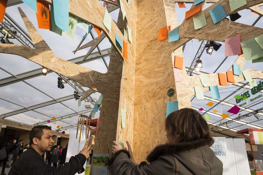 Attendees stick message notes on a tree sculpture at the United Nations COP21 climate conference.