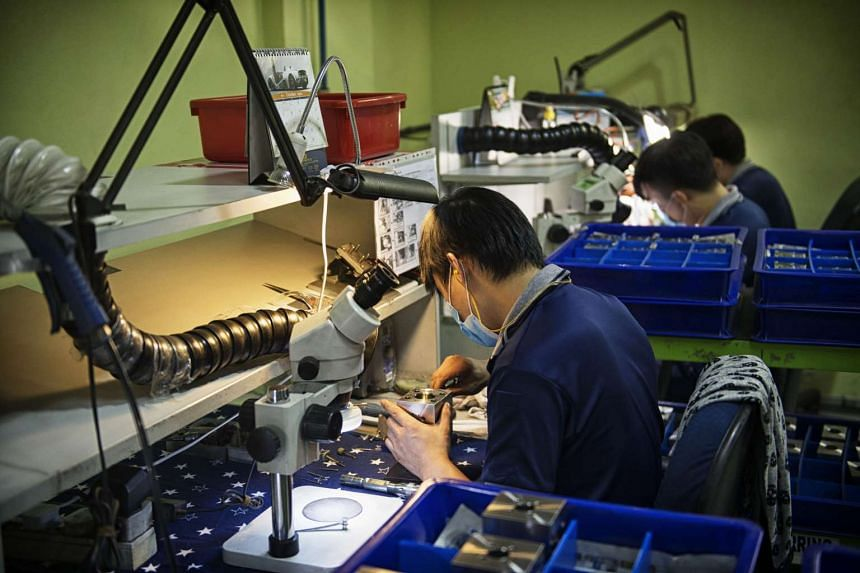An employee working on a machined metal component at a manufacturing facility in Singapore, on Oct 1, 2014.