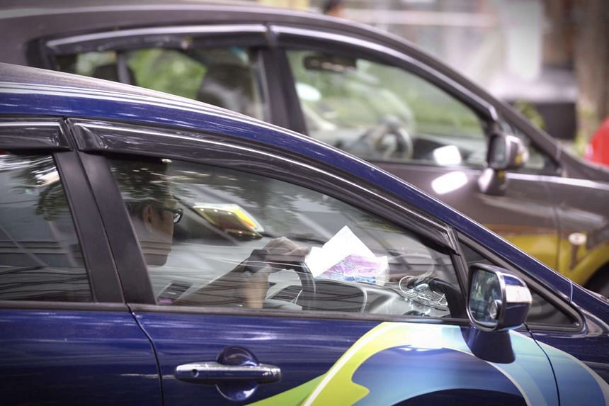 A driver using a mobile device along Orchard Road.