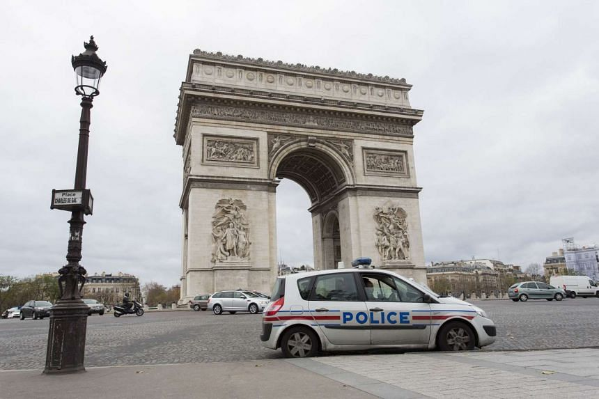 A police car stands opposite the Arc de Triomphe during the United Nations COP21 summit in Paris.