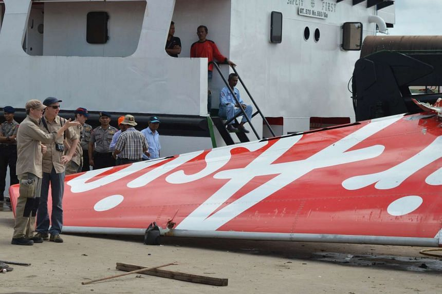 Foreign investigators examine the recovered tail of the AirAsia flight QZ8501 in Kumai on Jan 12, 2015.
