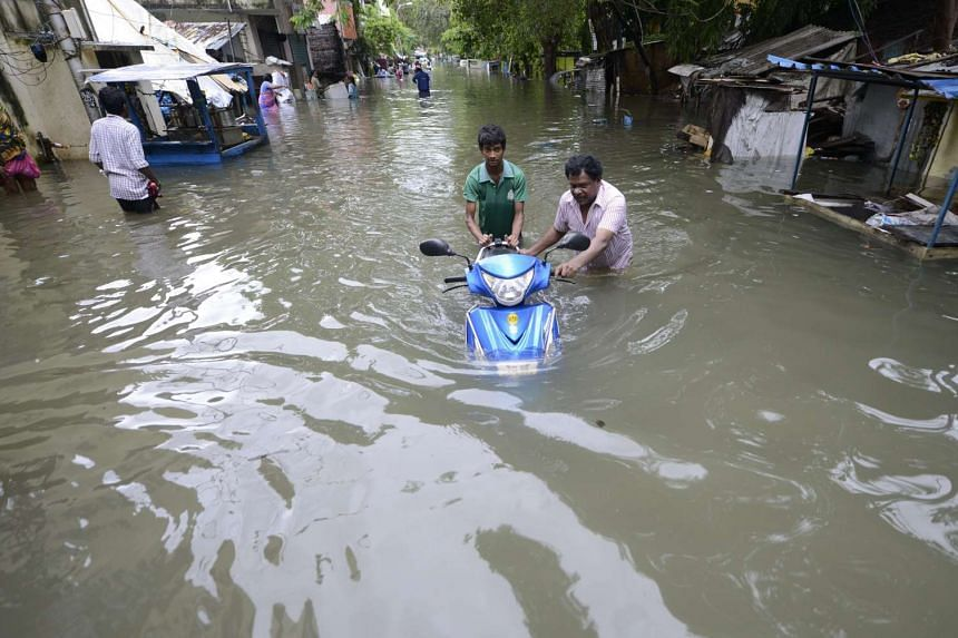 Two men push a scooter through flood waters in Chennai, India on Dec 2, 2015.