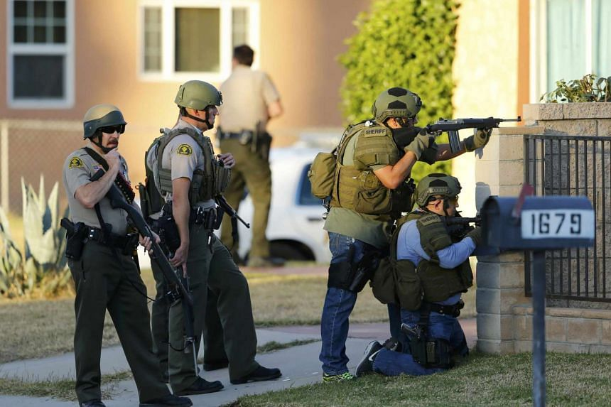 Police officers conduct a manhunt after a mass shooting in San Bernardino, California.