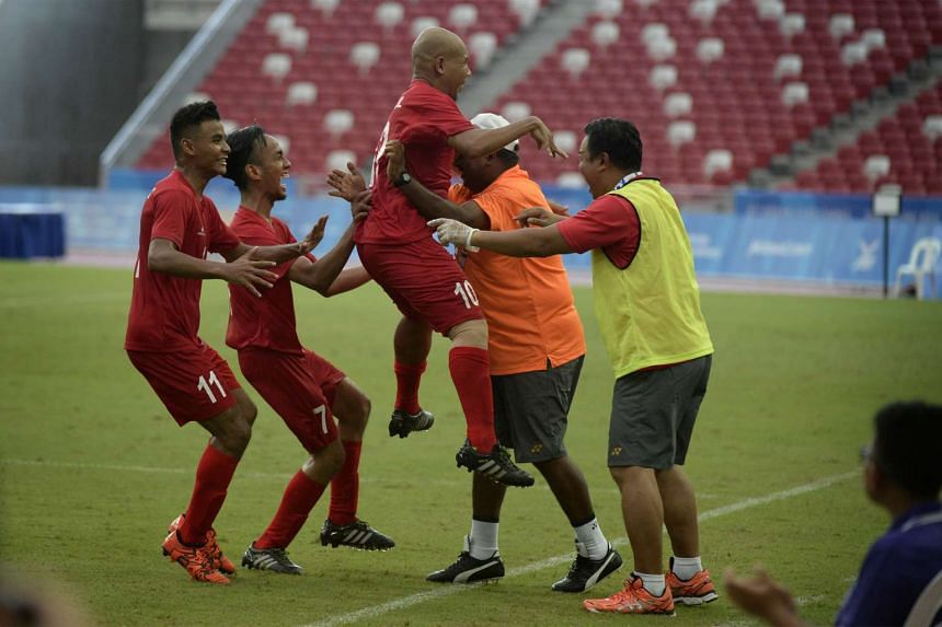 Khairul Anwar Bin Kasmani of Singapore (centre) celebrates with the team after scoring a goal against Indonesia during the Cerebral Palsy opening football match.