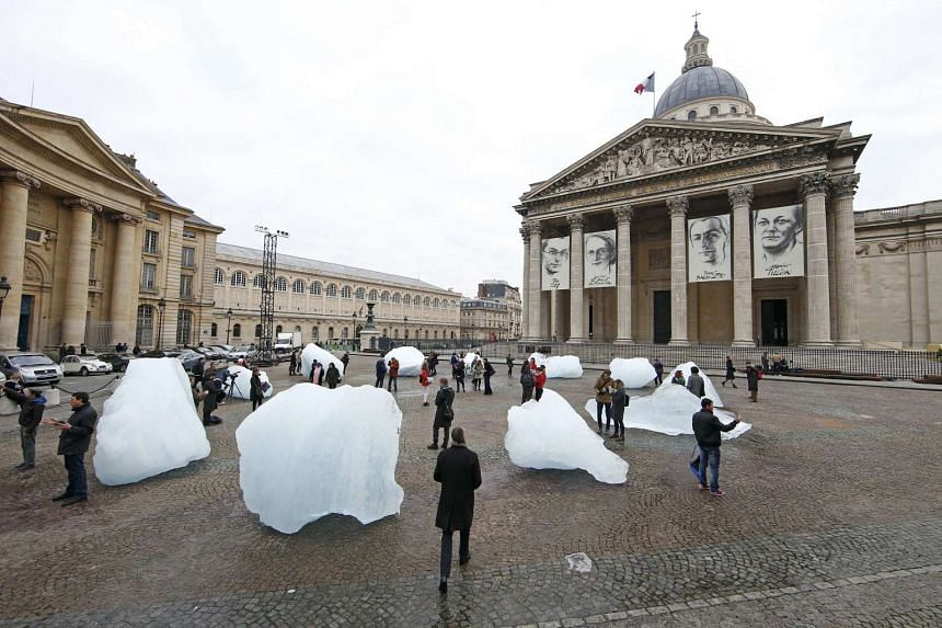 People walk through ice blocks harvested in Greenland and installed on the Place du Pantheon in Paris on Dec 3, 2015.