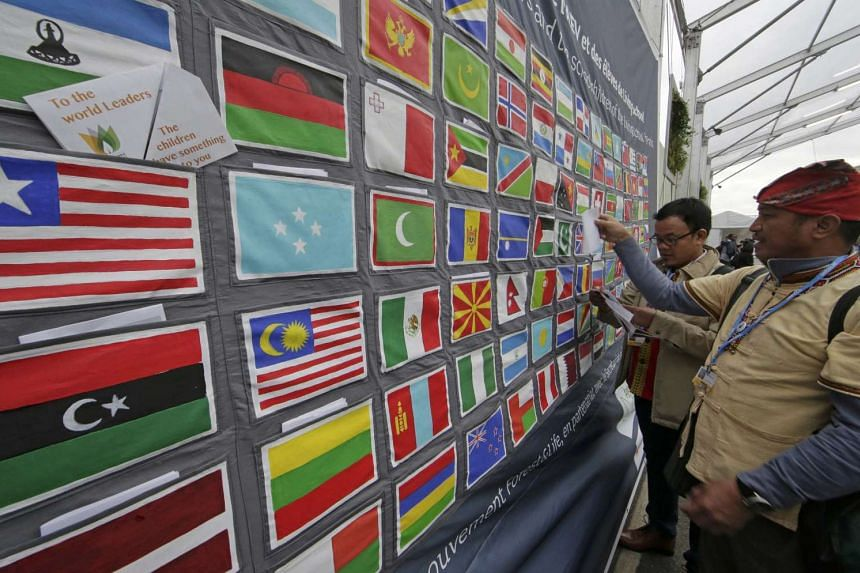 A visitor places a note to world leaders in a pocket on a giant flag-covered message board at the COP21.
