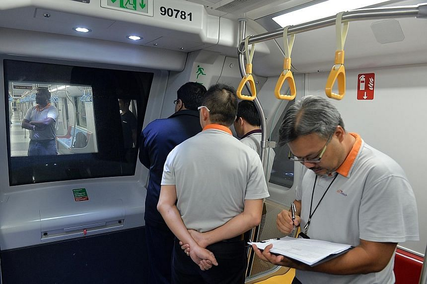 """A rescue train being used to push a """"stalled"""" train (left) between the Little India and Newton stations in a simulation of a train breakdown yesterday while SBS Transit staff (right) observe the train recovery exercise."""