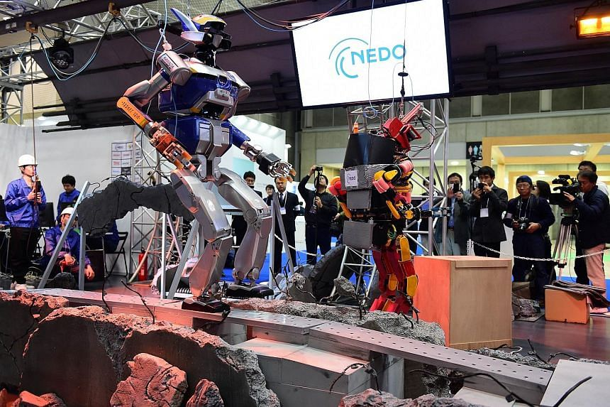 Humanoid robot HRP-2 (left) making its way through mock debris during a demonstration at the annual International Robot Exhibition in Tokyo yesterday. Japan, a country on the Pacific Rim of Fire, is developing robots to carry out dangerous work in di