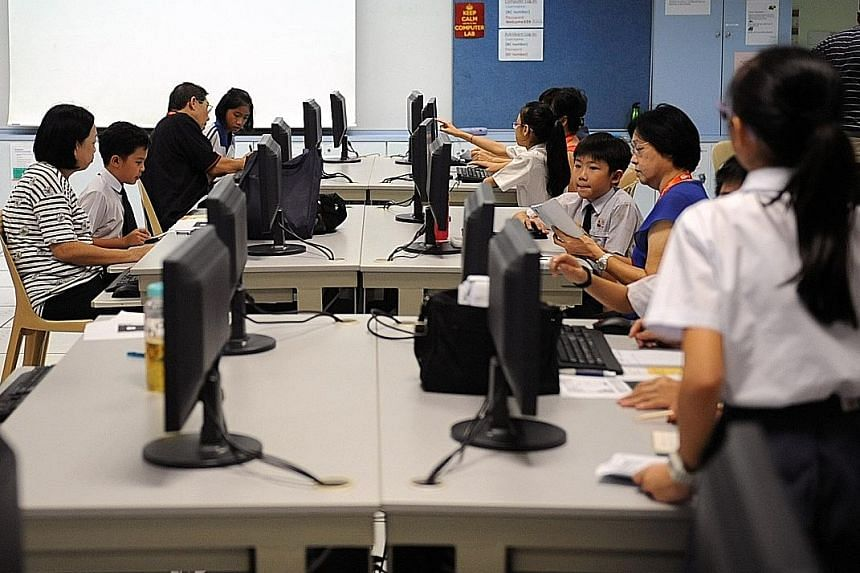 Seniors picking up computer skills at a school under a learning programme that pairs students with older learners. The latest report by the International Telecommunication Union says Singapore's ranking was pulled down by its adult literacy rate, and