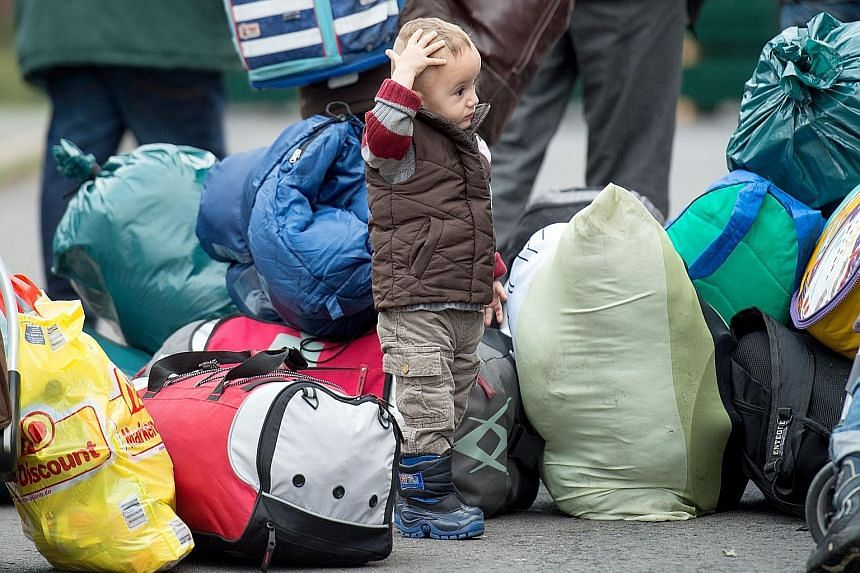 A bewildered boy at a first registration centre for refugees in Germany yesterday. Berlin and Paris support a quota system to redistribute migrants across EU members.
