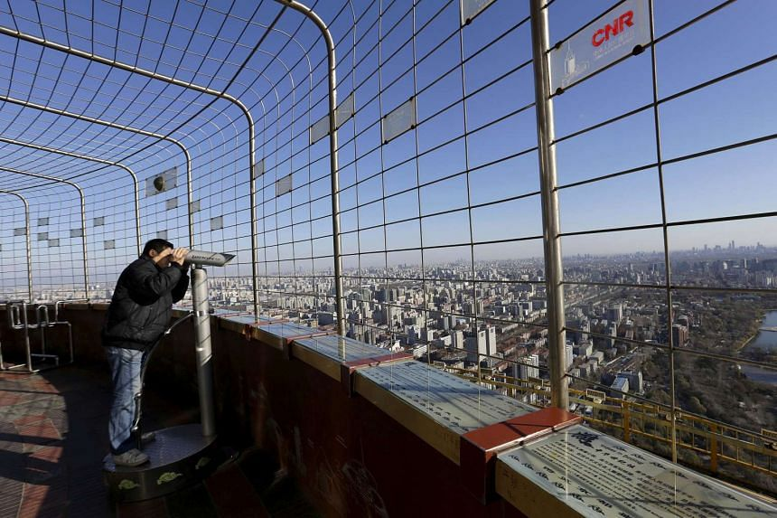 A visitor uses binoculars to see the city of Beijing at a viewing deck on a sunny day on Dec 2, 2015, after a fresh cold front cleared the smog that was blanketing Beijing, China.