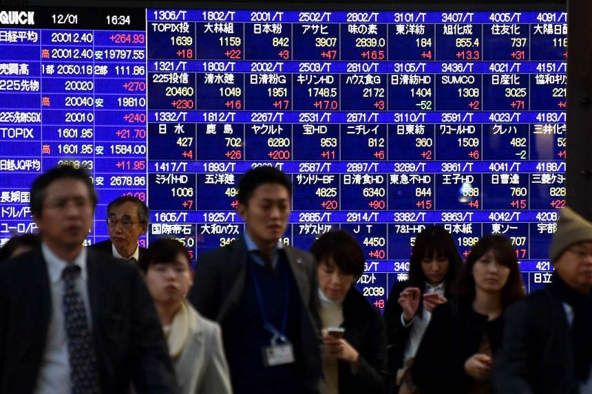 Pedestrians walking past a share prices board of the Tokyo Stock Exchange in Tokyo, Japan, on Dec 1, 2015.