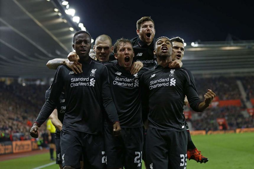 Divock Origi celebrates with team mates after scoring the fourth goal for Liverpool.