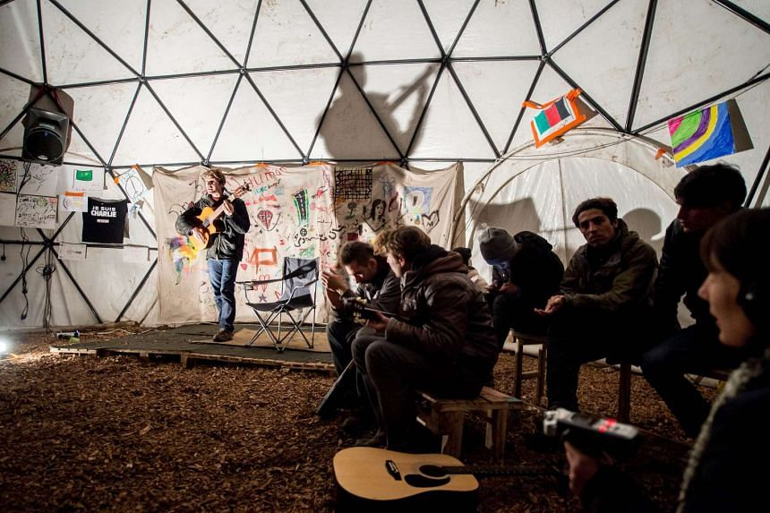 """Migrants listen to a guitarist performing in a makeshift theatre in the so-called """"Jungle"""" migrant camp in Calais."""