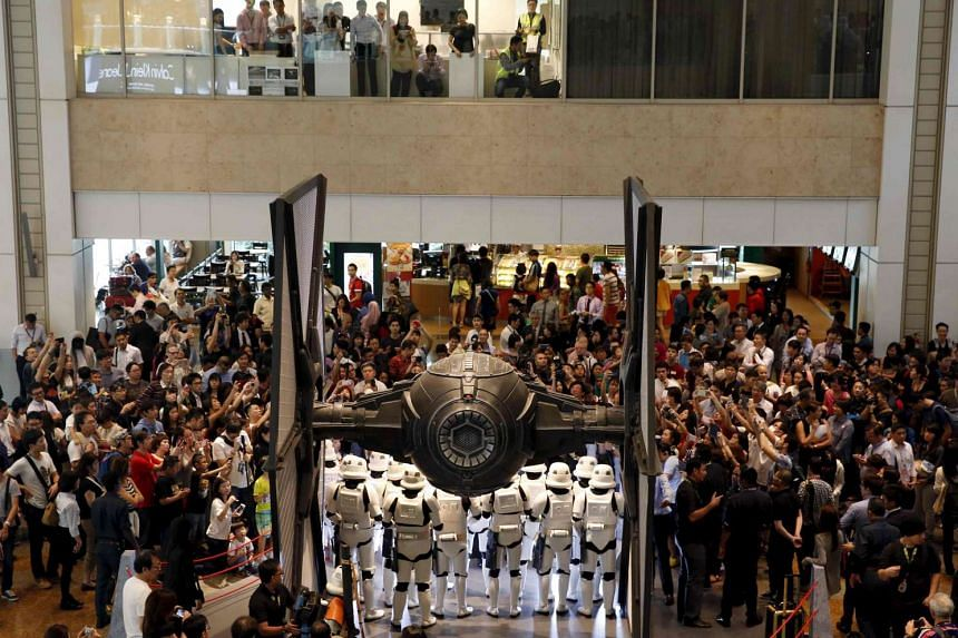 People take photos of Stormtroopers around a life-sized Star Wars TIE Fighter model on display at  Changi Airport last month.