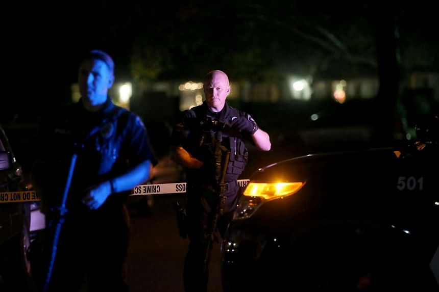 Redlands police officers stand guard as they investigate a suspicious vehicle on Dec 2, 2015, in Redlands, California.