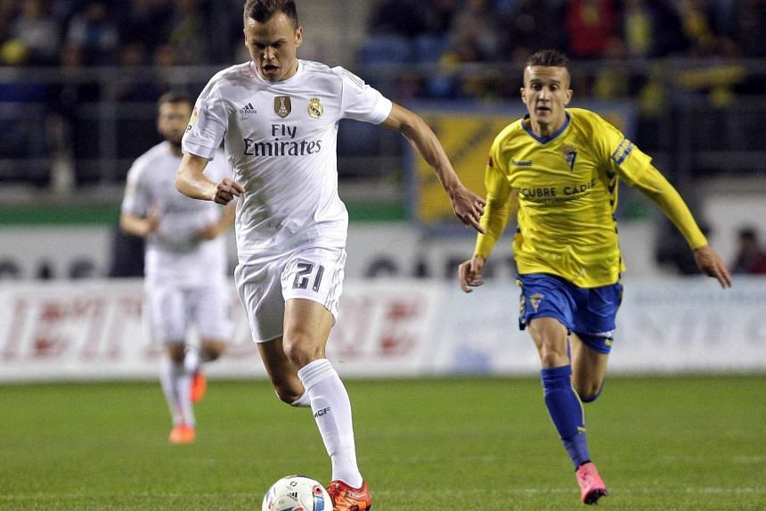 Real Madrid's Russian player Denis Cheryshev (left) and Sergio Martinez Mantecon of Cadiz FC in action during the King's Cup football match.