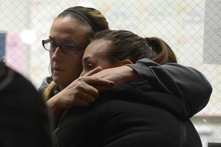 Evacuees at the Inland Regional Center hug each other as they wait inside the Rudy C Hernandez Community Center in San Bernardino, California, on Dec 2015.
