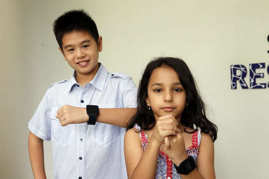 Ten-year-old Joshua Tham (left) and six-year-old Adira Kelath are part of a group testing a new wearable gadget for kids aged six to 12. It is meant to encourage children to spend more time outdoors, which is said to reduce the incidence of myopia.