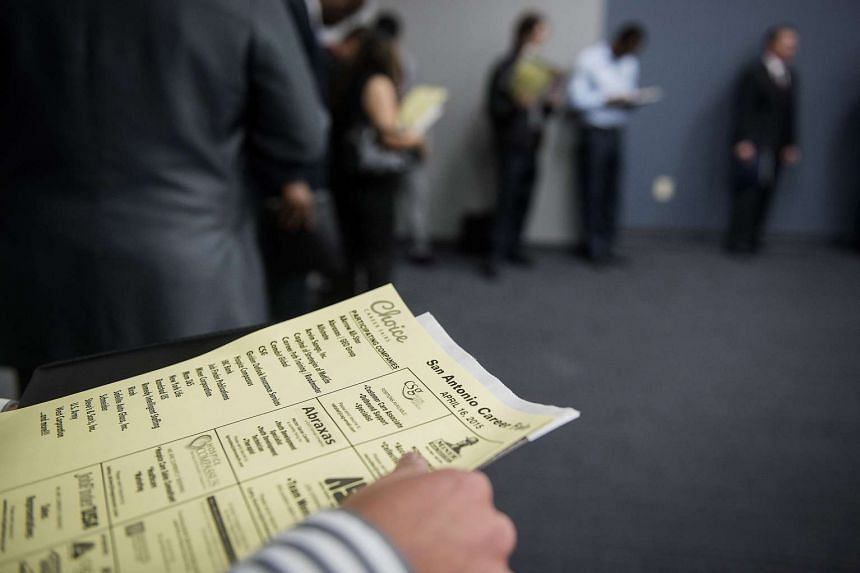 A job seeker holds an application while waiting in line to enter a career fair.