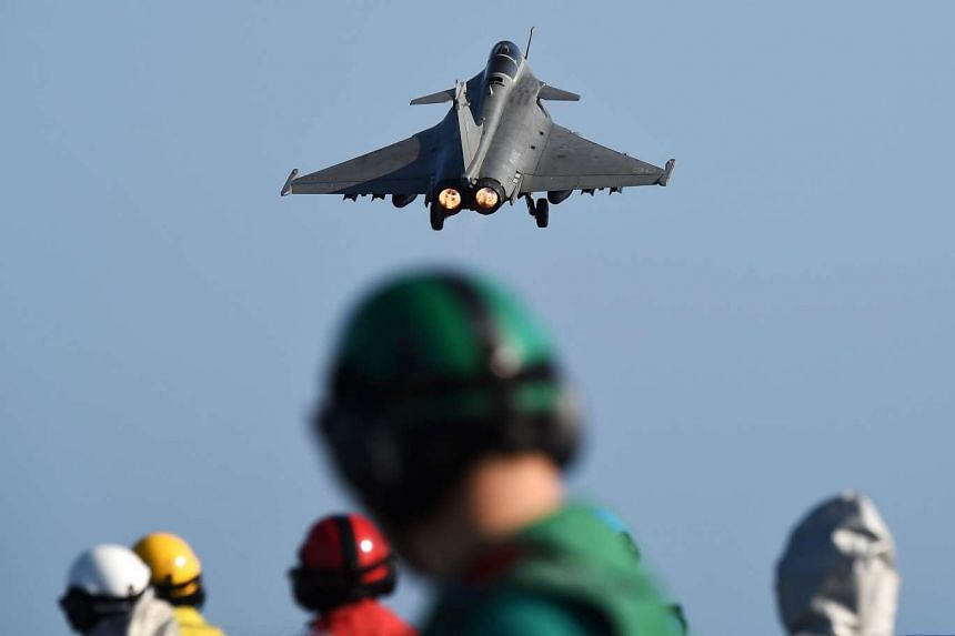 A French Rafale fighter aircraft takes off from a French aircraft carrier.