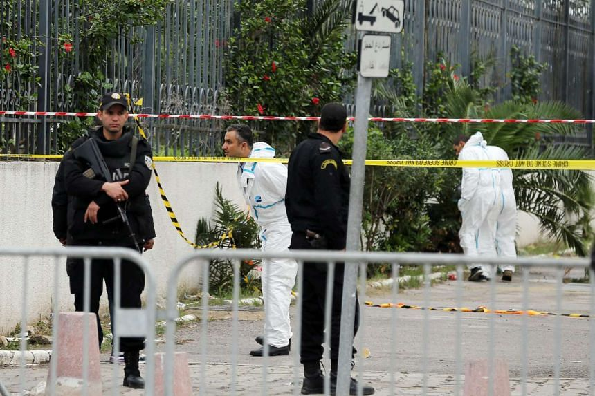 Tunisian forensic investigators inspect the scene in the aftermath of the bomb attack.