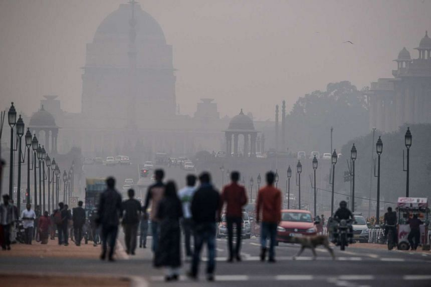 Indian pedestrians walk near smog enveloped government offices.