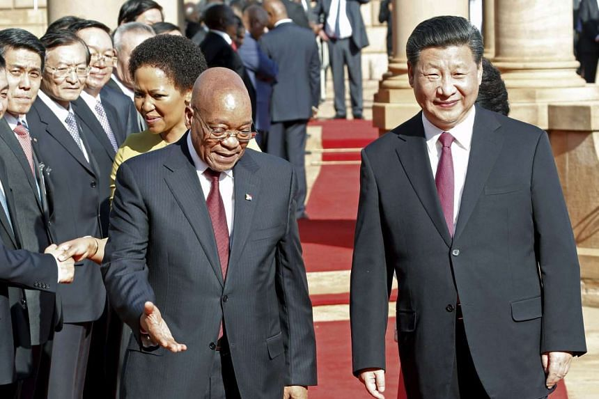 Chinese President Xi Jinping walks with South African President Jacob Zuma.