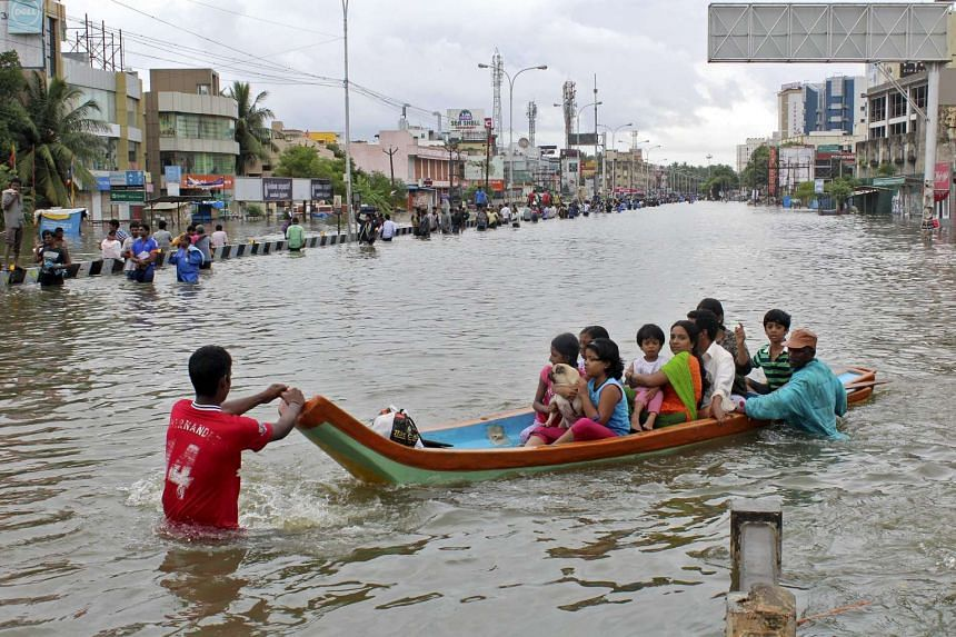 People travel on a boat as they move to safer places through a flooded road in Chennai.